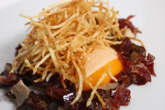 Yemas de huevo de caserío recubiertos de mozzarella con setas de temporada e ibéricos, aceite de trufa de la montaña alavesa y patatas paja